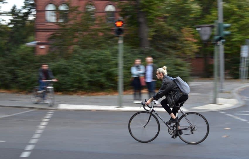 Mulher pedalando na rua com semáforo.