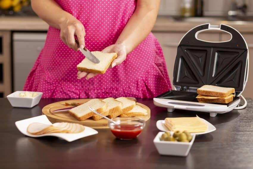 Mulher preparando sanduíches e colocando na sanduicheira.