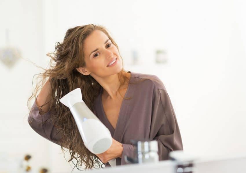 Imagem de mulher usando roupão secando o cabelo com secador de cabelo branco.