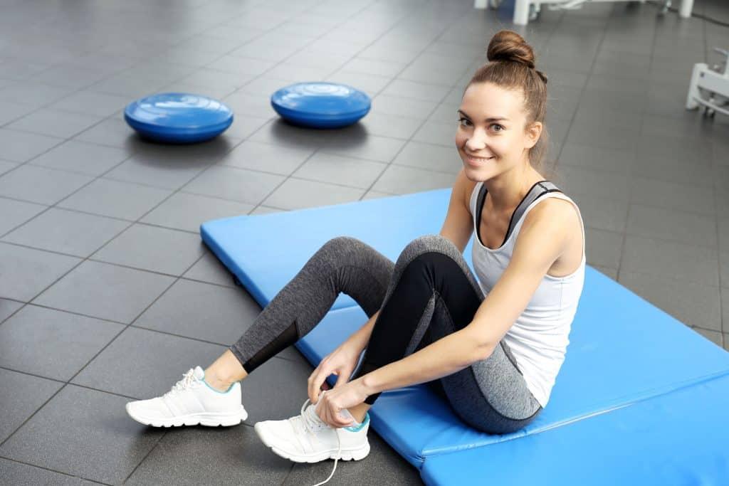 Mulher sentada em um colchonete azul na academia de ginástica.