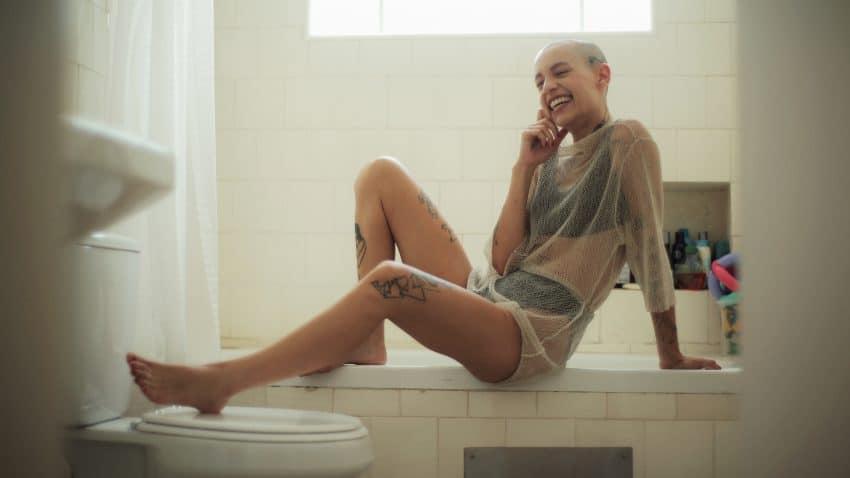Imagem de uma mulher tatuada sentada na beirada de uma banheira, vestindo uma blusa transparente com roupa íntima por baixo. Seu semblante é bastante sorridente.