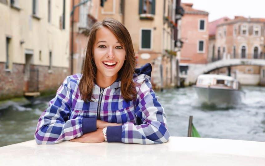 A foto mostra a boca de uma pessoa em close, ela está sorrindo e mostrando todos os dentes.