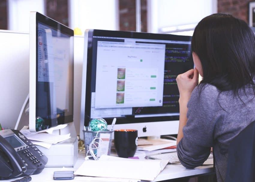 Garota de costas sentada em uma mesa de escritório em frente ao computador.