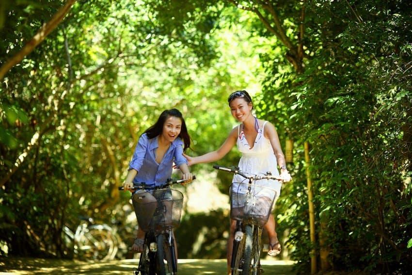 Duas mulheres andando de bicicleta em um parque.