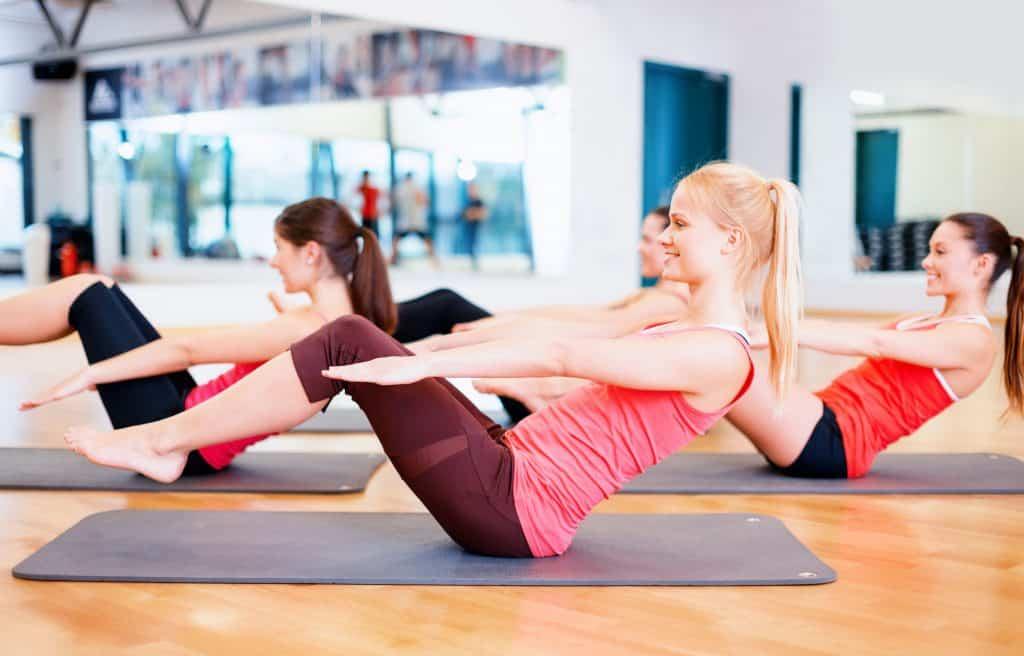 Imagem mostra mulheres fazendo exercício em cima de colchonete.