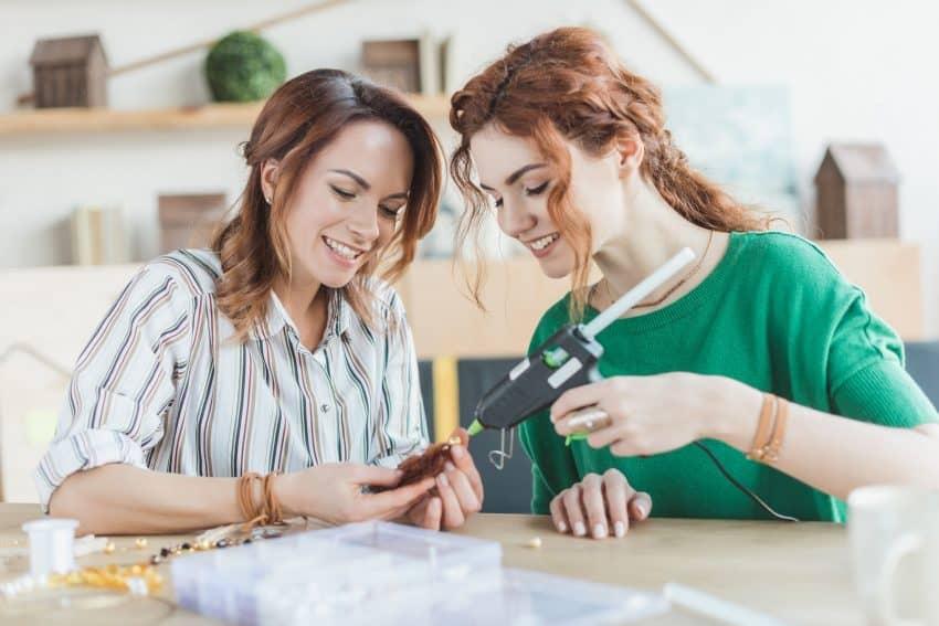 Duas mulheres fazendo bijuterias com uma pistola de cola quente.