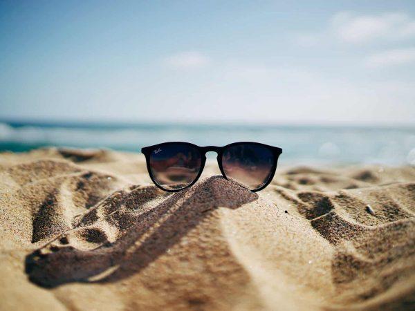Óculos de sol barato na areia praia.