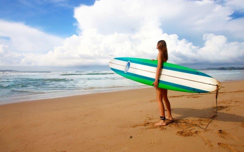 Imagem destaca uma pessoa descalça sobre a areia da praia, segurando uma prancha de surf modelo funboard, enquanto observa a formação das ondas no mar.