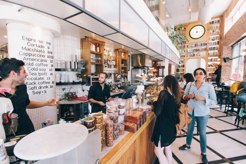 Imagem mostra uma padaria em que um homem está trabalhando no caixa enquanto outro homem conversa com ele, e algumas mulheres estão na fila para pagamento.