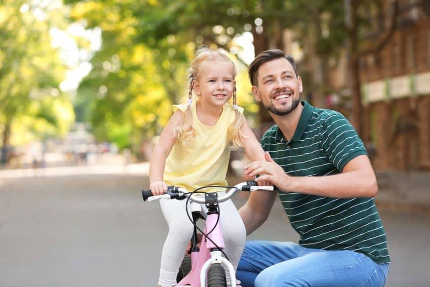 Pai ensinando filha a andar de bicicleta na rua.