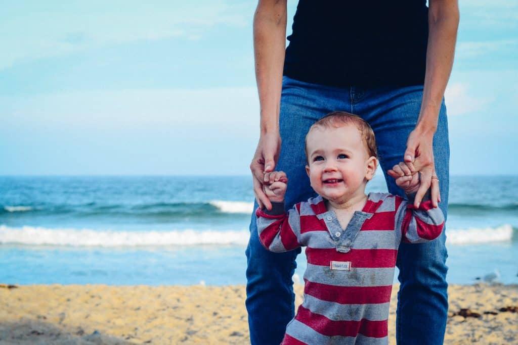 Pai segurando braços de bebê andando.