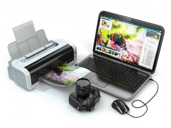 Imagem mostra uma impressora fazendo a impressão de uma foto em um papel fotográfico com notebook e câmera ao lado.