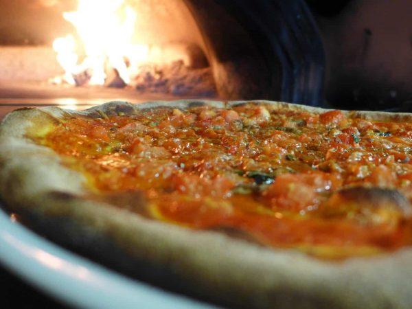 Close em uma pizza com molho de tomate e outros toppings em cima. Ao fundo, podemos ver um forno à lenha aceso.