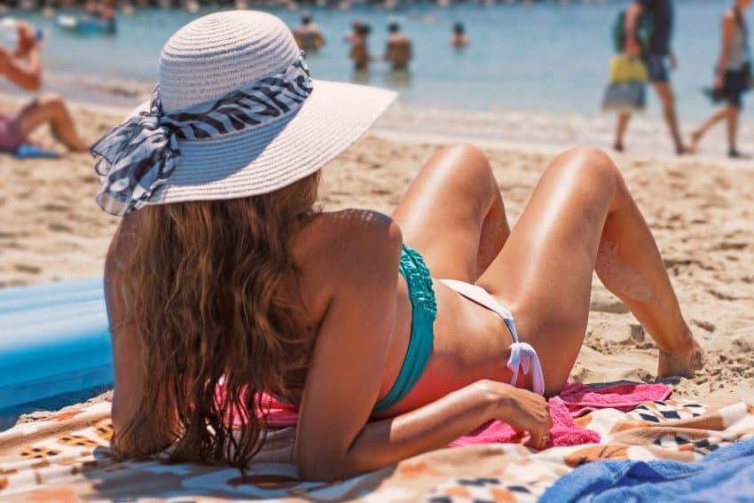 Imagem de uma mulher tomando sol em uma praia.