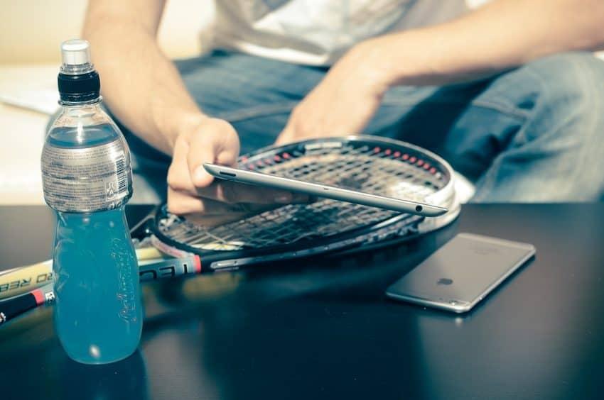 Imagem mostra uma pessoa com a mão apoiada em uma raquete de squash que está em cima de uma mesa, segurando um celular e com uma garrafa ao lado.
