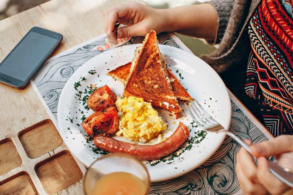 Na foto mostra-se um pedaço de uma mesa de madeira com um jogo americano embaixo de um prato contem pão tostado, ovos mexidos, tomates assados e uma salsicha. Sentada atrás do prato está uma mulher com a mão segurando um garfo.