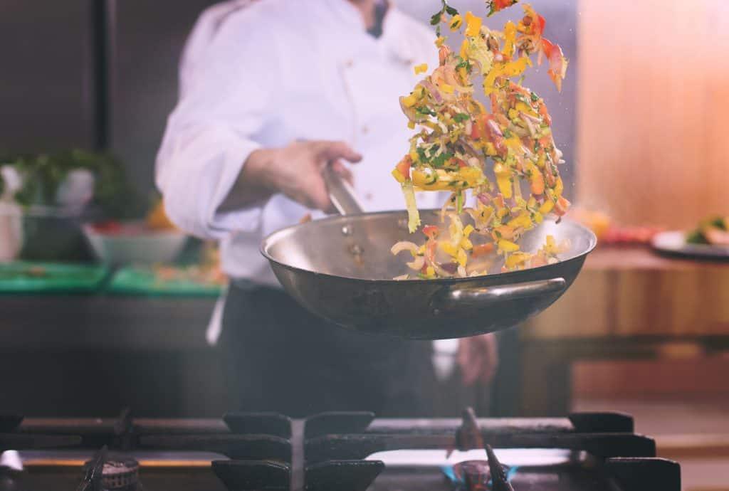 Foto de pessoa segurando panela wok com comida dentro e a jogando para o alto.