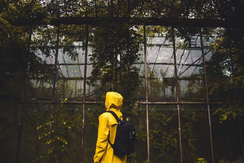 Imagem de pessoa de costas com capa de chuva amarela e mochila.