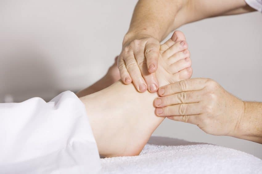 Na foto os pés de uma pessoa recebendo massagem.
