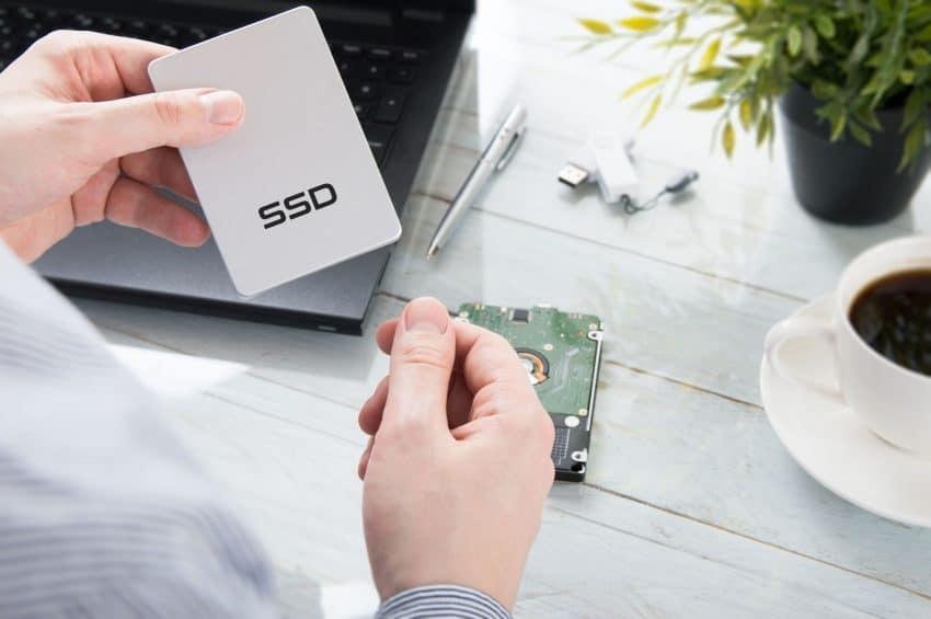 Homem segurando um SSD, ao fundo tem um notebook, uma planta, uma caneta, uma xícara de café e outros objetos sobre a mesa.
