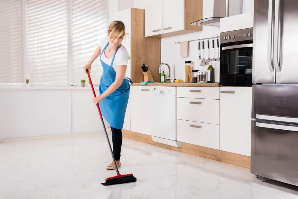 Imagem mostra mulher varrendo chão de cozinha.