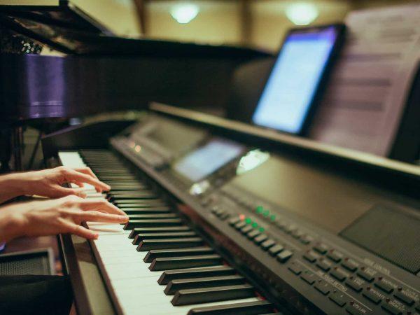 Close em piano digital. Há duas mãos nas teclas e, acima do piano, partituras e um tablet.