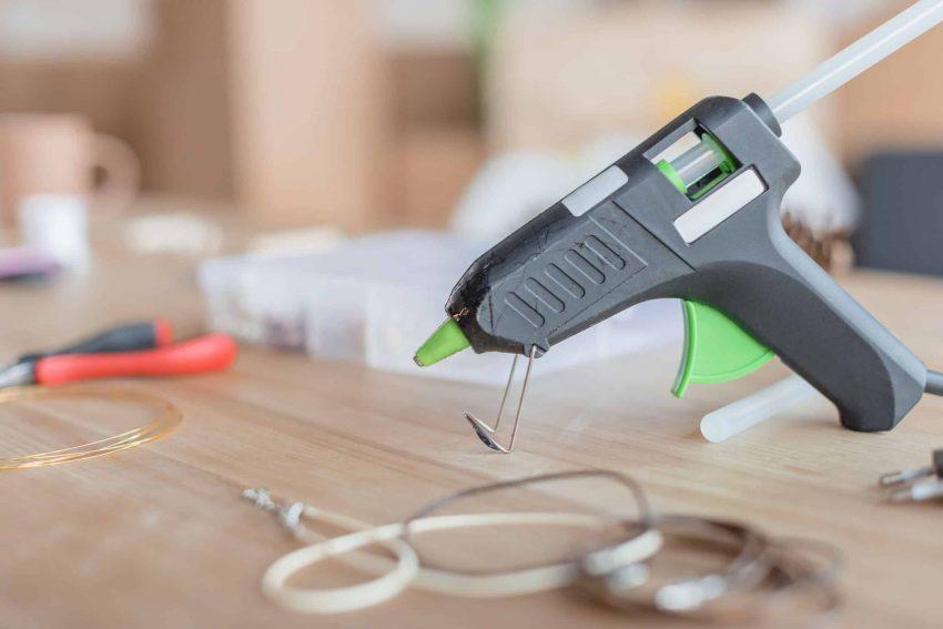 Uma pistola de cola quente posicionada sobre uma mesa.