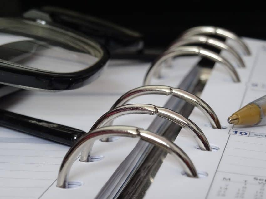 Fichário do modelo agenda aberto com óculos por cima.