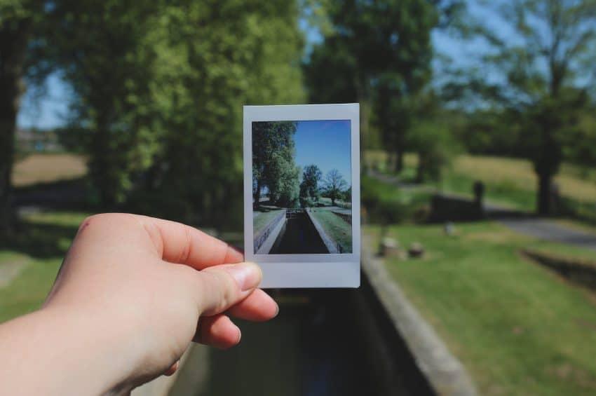 Imagem mostra a mão de uma pessoa segurando uma foto impressa na frente ao local onde ela foi tirada.