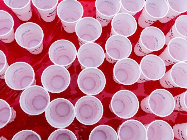 Diversos copos de plástico com água em cima de uma mesa.