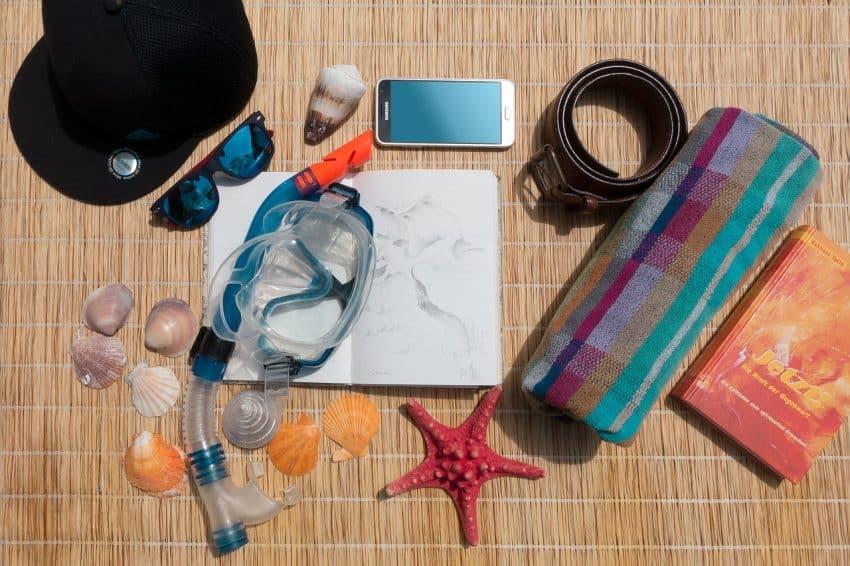 Objetos de praia em cima de uma esteira de palha.