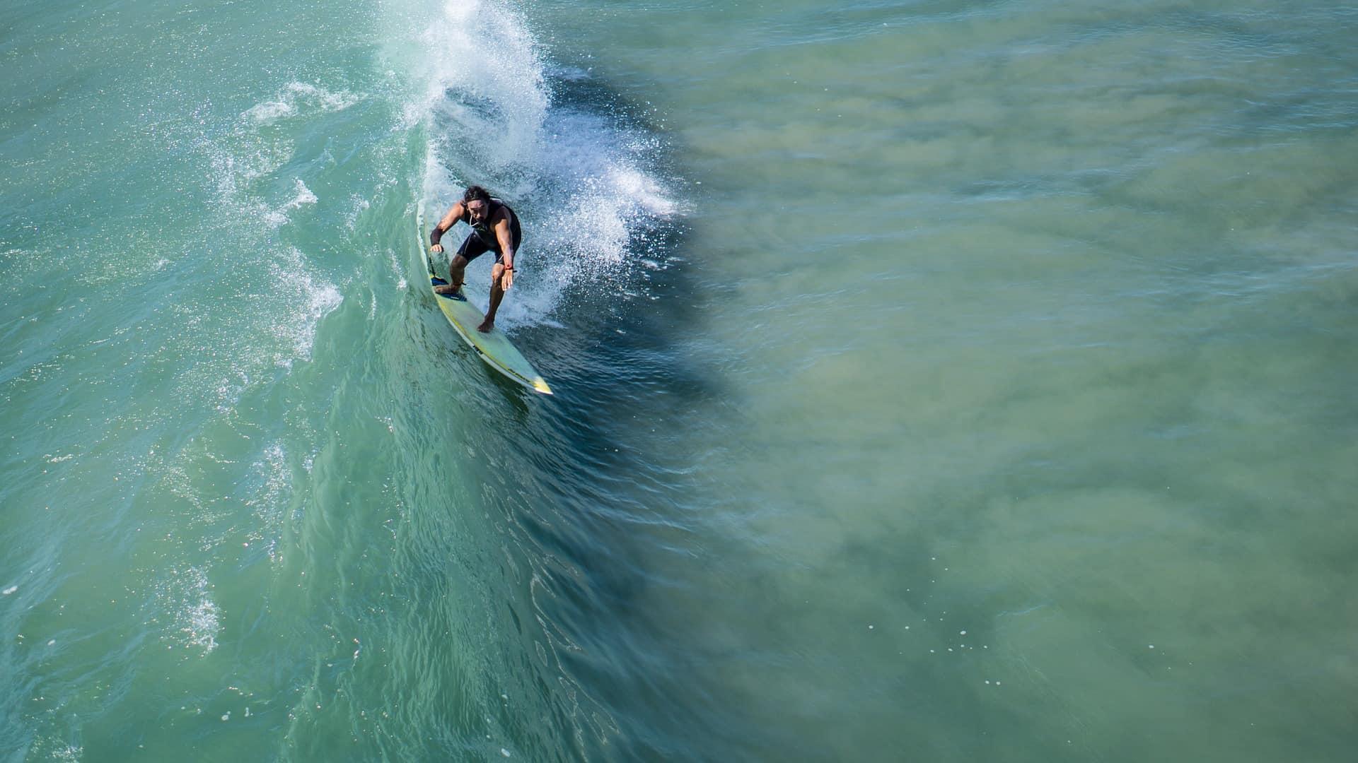 Imagem destaca um homem em uma prancha de surf deslizando sobre a crista de uma onda.