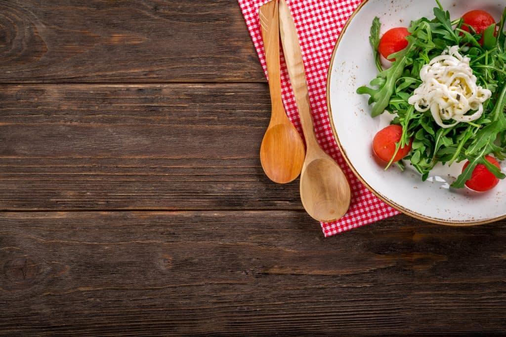 Na foto estão duas colheres de pau ao lado de um prato branco com uma salada de folhas e tomate em cima de um jogo americano quadriculado vermelho.