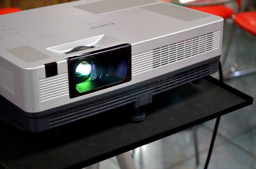Imagem de um projetor em funcionamento sobre uma mesa.
