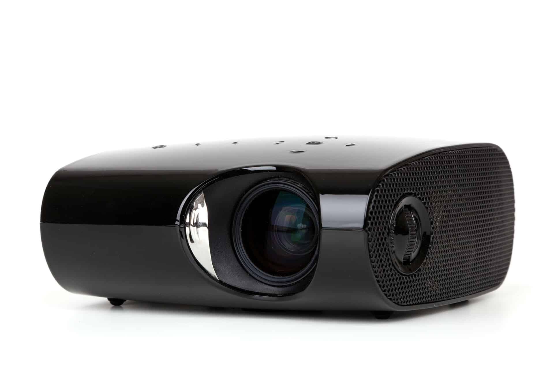 Imagem de projetor preto sobre superfície branca.