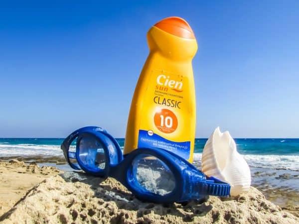 Imagem de um protetor solar na areia da praia ao lado de um óculos de natação.