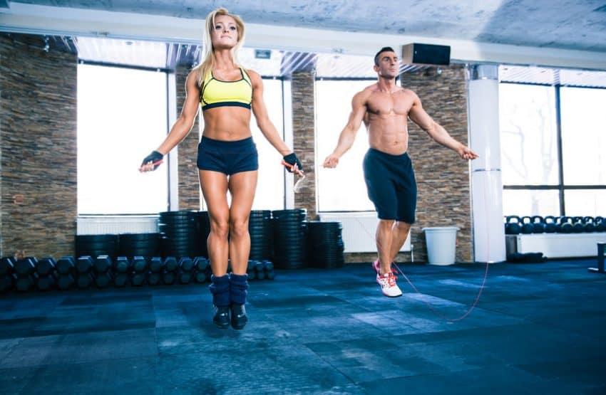Foto de uma mulher e um homem definidos pulando corda em uma academia.