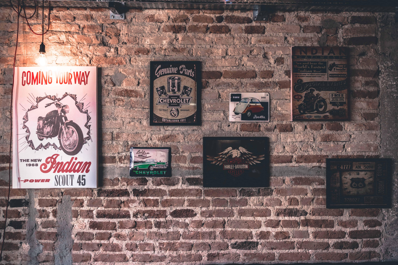 Foto de uma parede de tijolos, sem acabamento, com setes quadros decorativos dispostos.