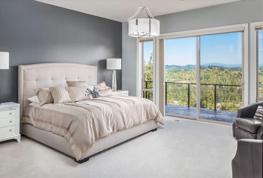 Imagem de quarto amplo com cama grande e cabeceira rosa.