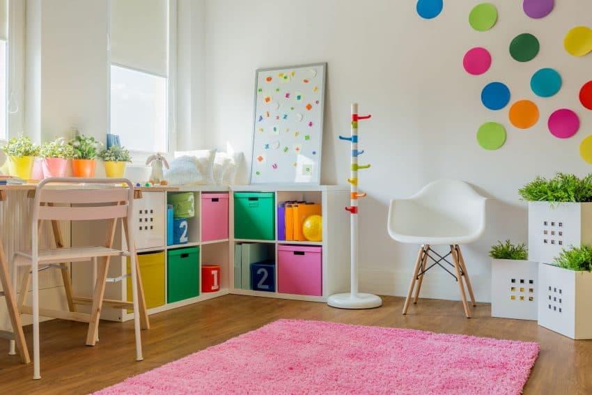 Quarto infantil bem decorado com quadro magnético ao fundo.
