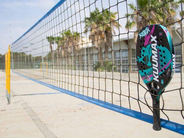 Imagem mostra uma raquete de beach tennis pendurada na rede de jogo em uma quadra de praia.