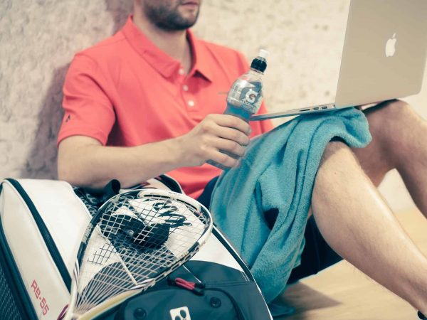 Imagem mostra um homem sentado no chão com um notebook no colo e com uma raquete de squash e uma bolsa esportiva ao seu lado.