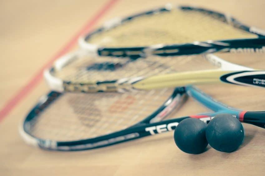 Imagem mostra três raquetes de squash junto a duas bolinhas no chão.