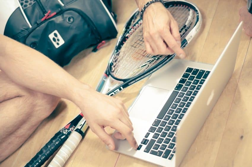 Imagem mostra uma pessoa utilizando um computador e junto a ele há duas raquetes de squash.