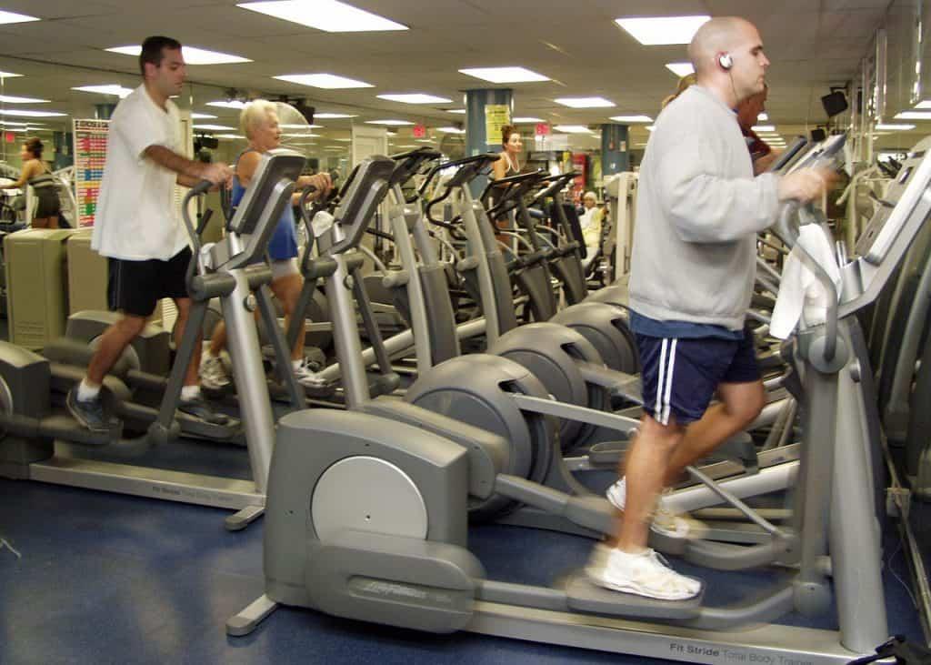 Imagem mostra pessoas utilizando aparelhos elípticos durante exercícios em academia.