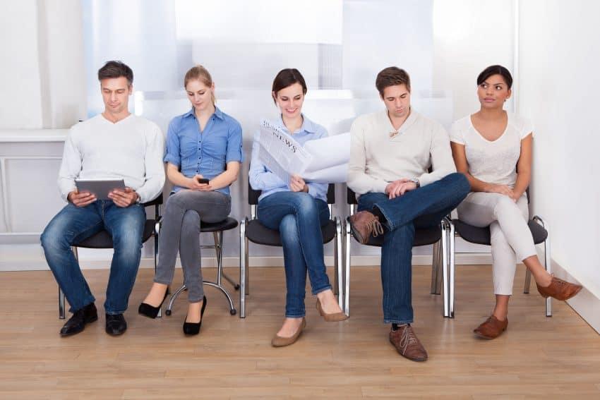 Cinco pessoas aguardando em uma sala de espera.