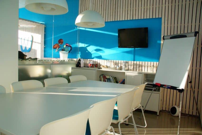Imagem de uma sala de reuniões como uma televisão instalada em uma parede.