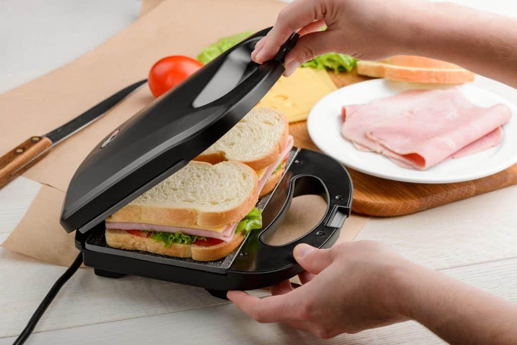 mão preparando sanduíches na sanduicheira