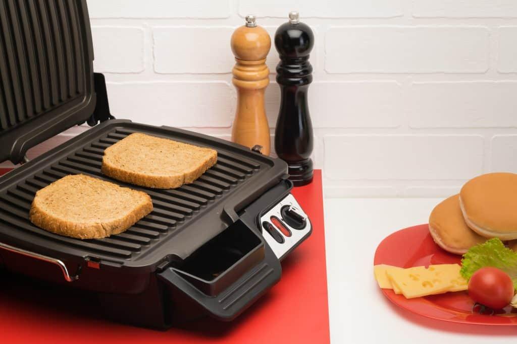Dois pedaços de pão torrando na sanduicheira, há um prato ao lado e temperos ao fundo
