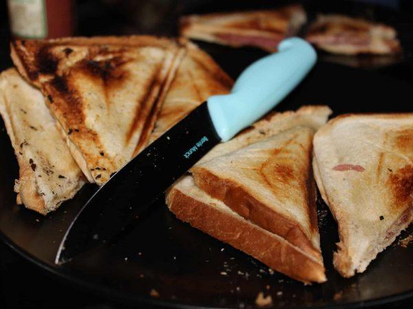 Imagem de dois sanduíches no estilo misto quente, e uma faca com cabo azul entre eles.